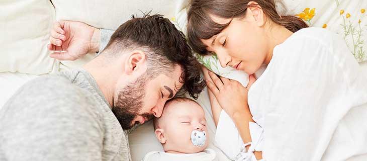 Parent avec un nouveau né prend un repos dans un lit.