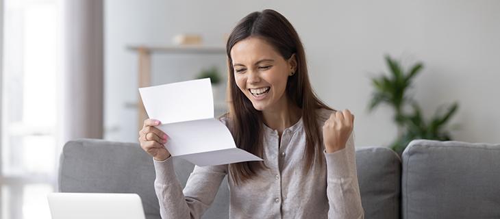 Etudiante lisant une lettre avec un sourire courageuse, sa main dans un point de félicitation.
