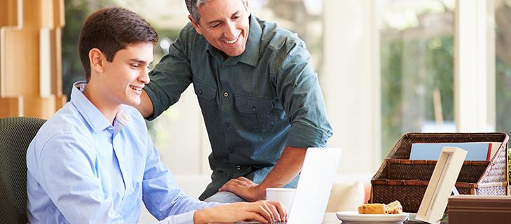 Un père aidant son fils sur son ordinateur portable.