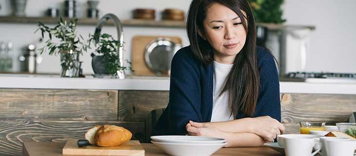 Une femme en train de penser avec les bras croisés à une table.