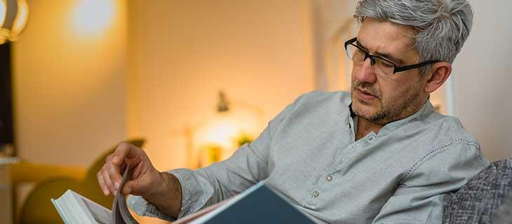 Un homme mature est assit sur un canapé lisant un livre.