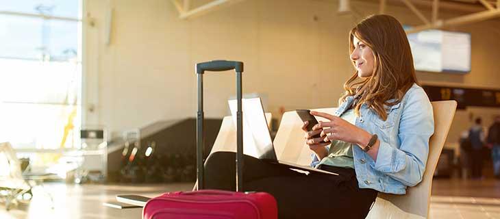 Une étudiante assise à l'aéroport avec son ordinateur portable et un téléphone cellulaire en mains.