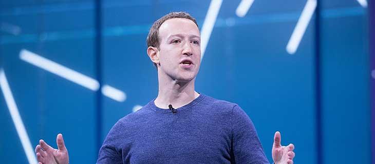 Un homme sur un stage en train de parler avec les bras grand ouvert.