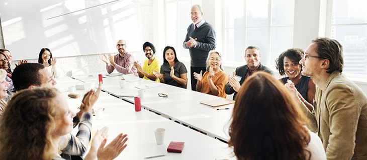 Réunion avec des membres professionnelle applaudissant leurs main a l'entour d'un bureau.