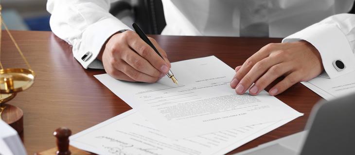Un homme stylo plume en main, signe des documents.