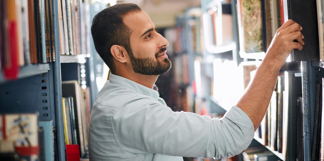 Un jeune homme regardant des livres dans une bibliothèque.