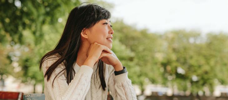 Femme assis dehors entrain de pensée contentement.