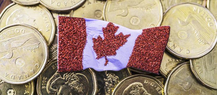 Un drapeau canadien placé au-dessus d'une pile d'argent en or.