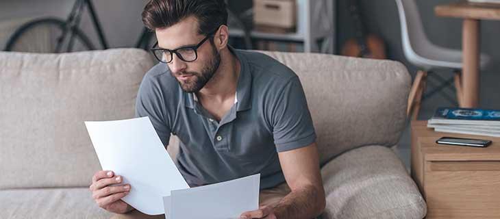 Jeune homme assis sur un canope regardant des papier avec son téléphone portable sur la table a coté de lui.