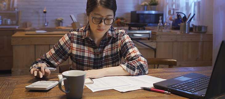 Une femme assise devant son ordinatuer portable qui fait ces impôts avec une calculatrice.