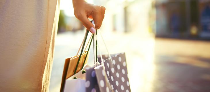 Main d'une madame tenant des sacs de magasins.