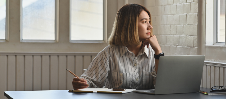 Une étudiante devant son portable regardant dehors.