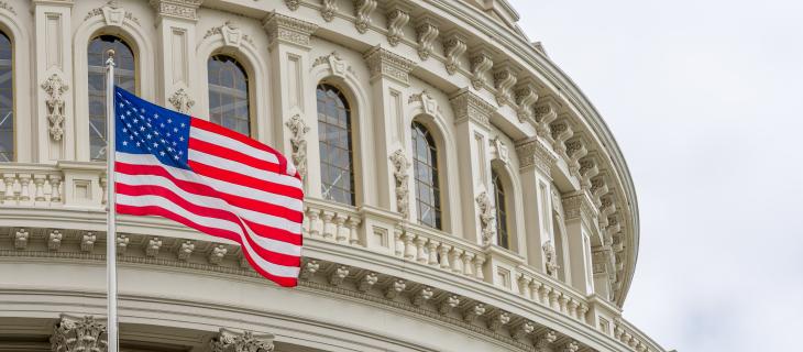 Un drapeau américain devant un édifice blanc.