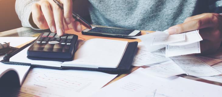 La main d'une personne qui utiliise une calculatrice pour faire ses impôts.