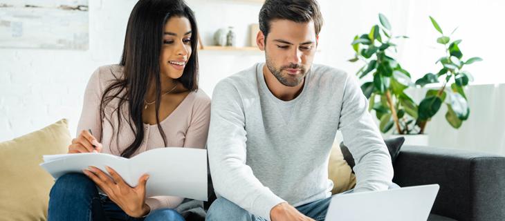 Jeune couple regardant l'information sur un portable assis sur un canope.