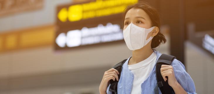 Une jeune femme dans un aéroport portant un masque de protection.