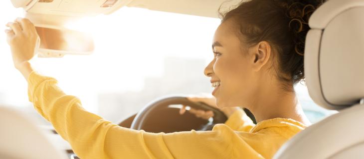 Jeune fille conduisant regarde dans son miroir d'engluement.