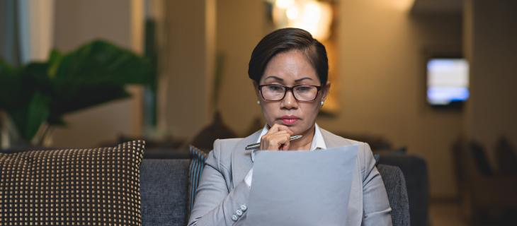 Une femme professionnelle lit des documents sérieusement.