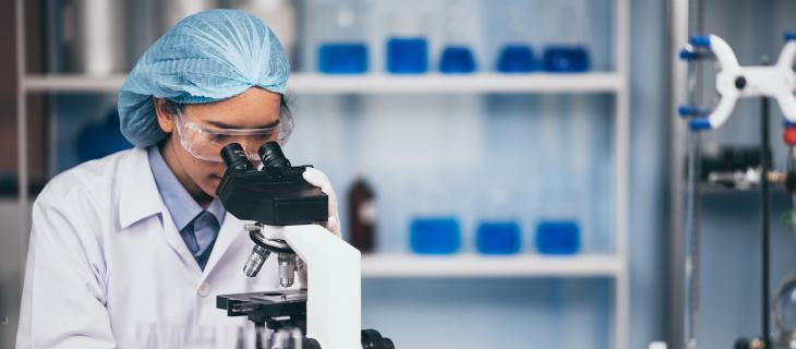 Un professionel de la santé dans un laboratoire porte une protection personnelle et regarde dans un kaléidoscope.