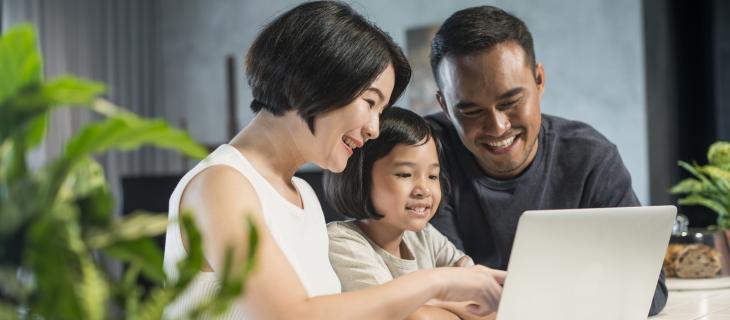une famille assise à une table regardant un ordinateur portable.