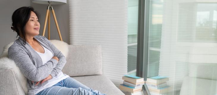 Femme mature assise sur un canope blancs regarde dehors, avec des livres à côté d'elle-même.