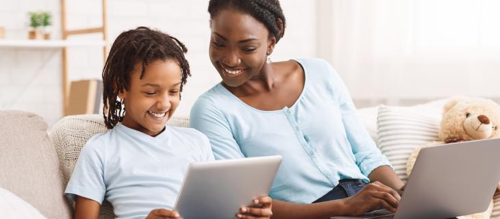 Une mère et sa fille assise sur un canapé chacune sur leur ordinateur portable.
