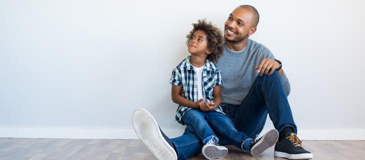 Jeune père souriant assis sur le plancher avec son fils.