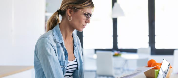 Une femme professionnelle regardant des documents devant son ordinateur portable.