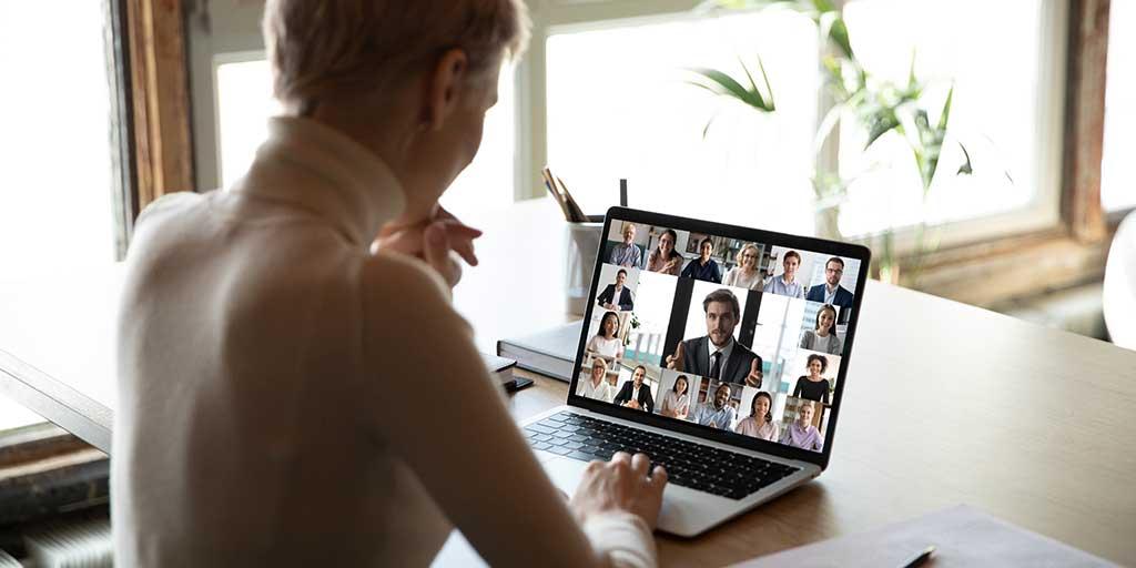 Une femme assise à une table en train de faire un appel vidéo sur un portable.