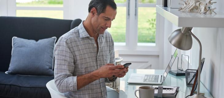 Un homme professionnel travaillant à domicile à l'aide d'un téléphone portable.