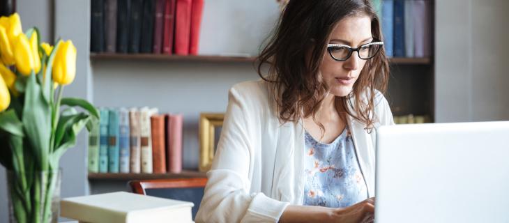 Une femme professionnelle dans un bureau qui travaille sur son ordinateur portable.