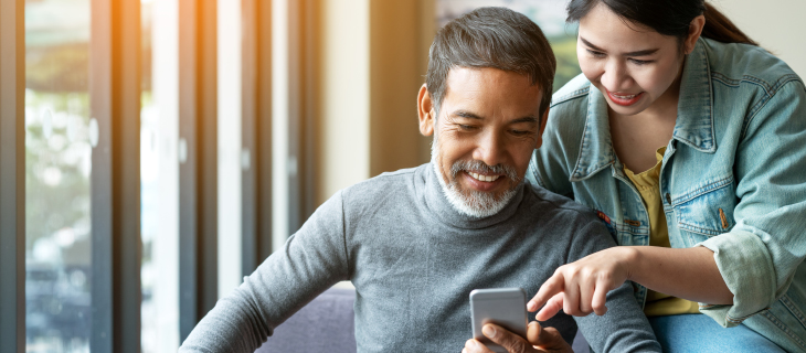 Un homme mature montre son téléphone portable avec une jeune mademoiselle.