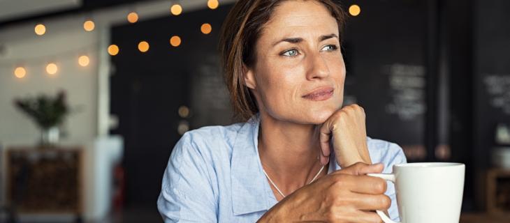 Une femme regarde dehors en buvant son café.
