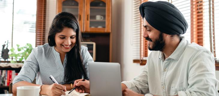 Un couple regardant des documents devant un portable.