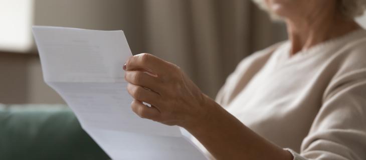 Une madame âgée lisant un papier dans ces mains.