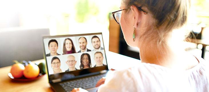 Femme assis a une table entrain de faire un appel vidéo sur un portable.