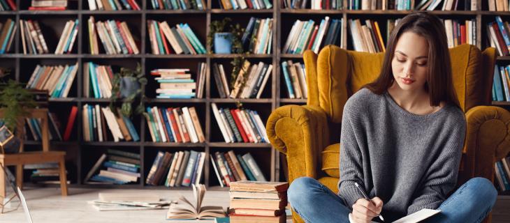 Etudiante dans un bibliothèque entrain d'étudier assis sur une chaise jaune.