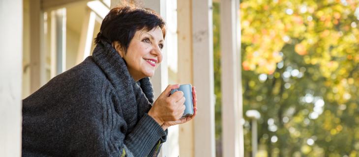 Femme âgée tenant un verre dans ces main accotant sur son balcon regardant dehors souriant.