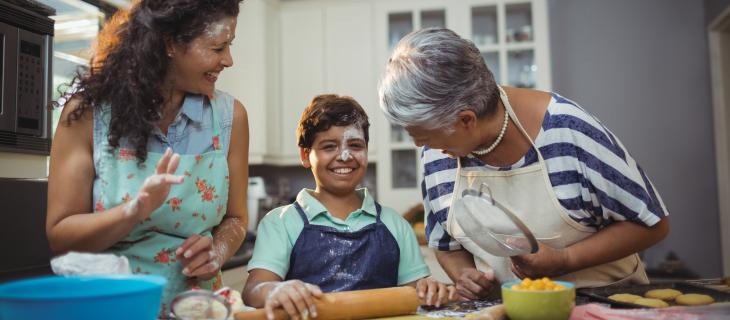 Grand'mère, mère et petit fils cuisant dans la cuisine.