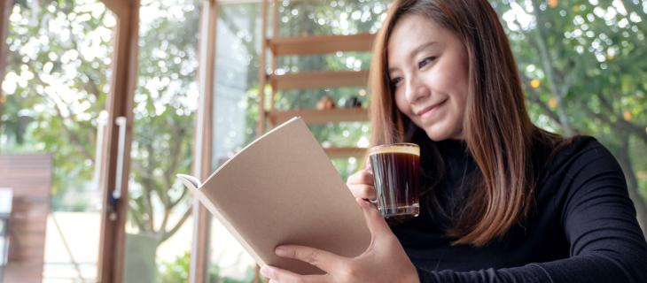 Femme lisant un livre en buvant.