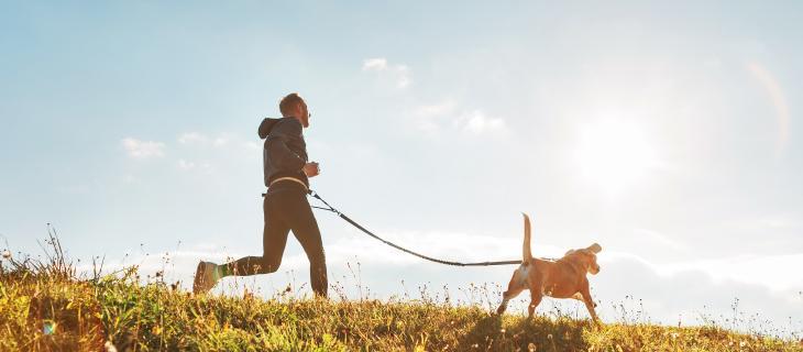 Un homme qui cours dehors avec son chien.