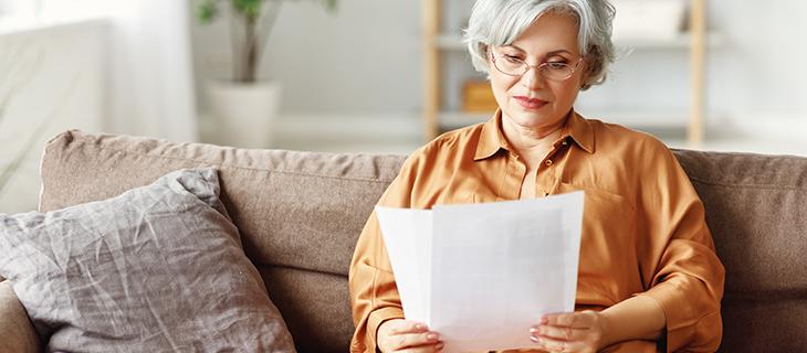 Une madame âgée regardante à un papier assise sur un canapé.