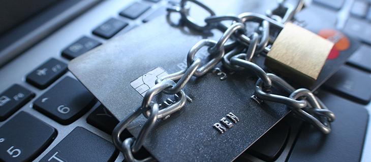 Une carte bancaire sur un portable avec un cadenas barrant la carte.