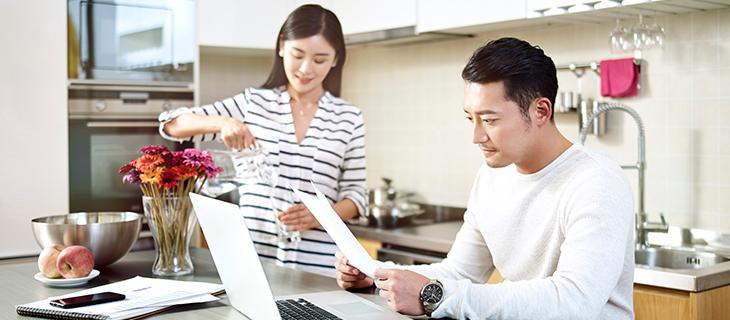 Un homme et femme dans la cuisine, l'homme travail sur un portable et la femme verse un verre d'eau.