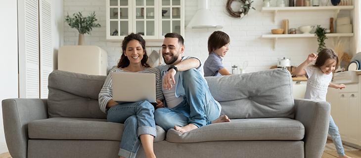 Des parents sur un ordinateur portable et les enfants jouent dans le salon.