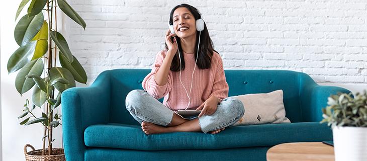 Une jeune femme souriante avec les yeux fermé sur un canapé avec des écouteurs.