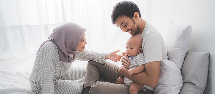Une jeune famille est  assis sur un lit avec un nouveau née.