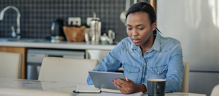 Jeune femme utilisant une tablette numérique à la maison