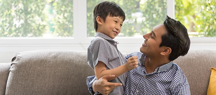 Un père souriant regardant son petit fils.