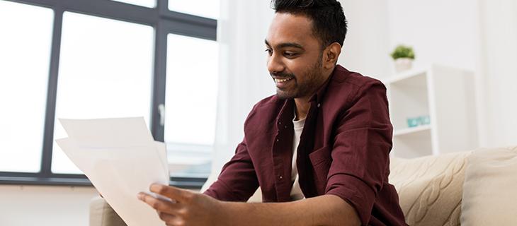 Un jeune homme assis sur un canapé regardant des documents.